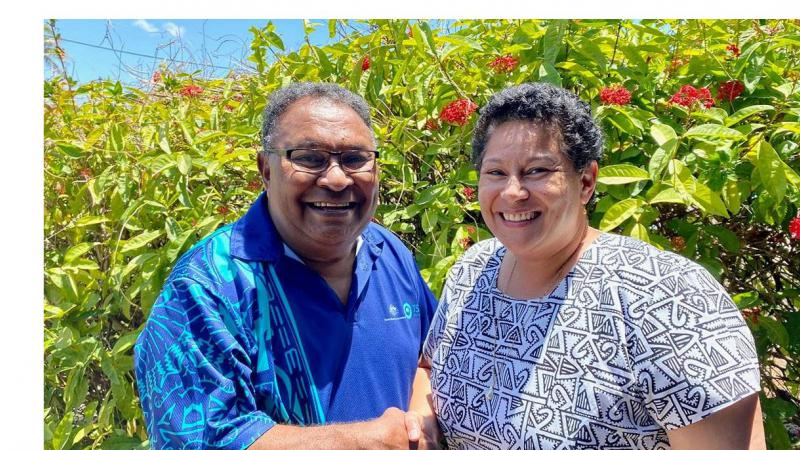 Indigenous man in blue shirt shakes hand of Indigenous woman in white dress with black pattern. In the background is a green hedge with red flowers.