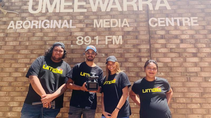 Four Aboriginal young adults (2 men and 2 women) in black t-shirts with UMEEtv printed on them stand in front of a brick wall. On the wall are the words: Umeewarra Aboriginal Media Centre 89.1 FM