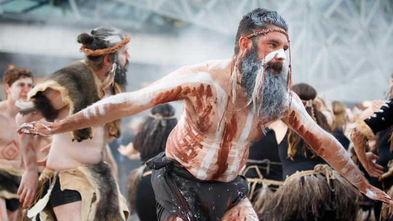 Men and women in traditional Indigenous dress and paint dance and face in different directions. In the background is smoke and a lattice of metal work in a building.