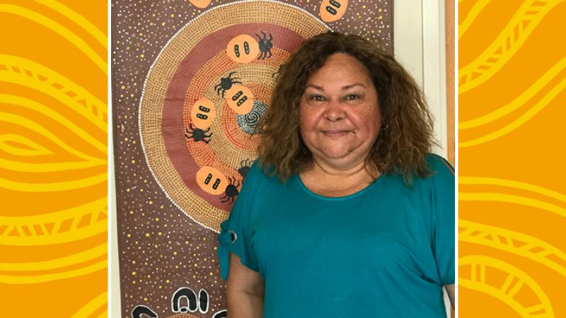 Indigenous Primary School teacher standing front of Indigenous artwork of Honey ants and dots in circles on a brown background.