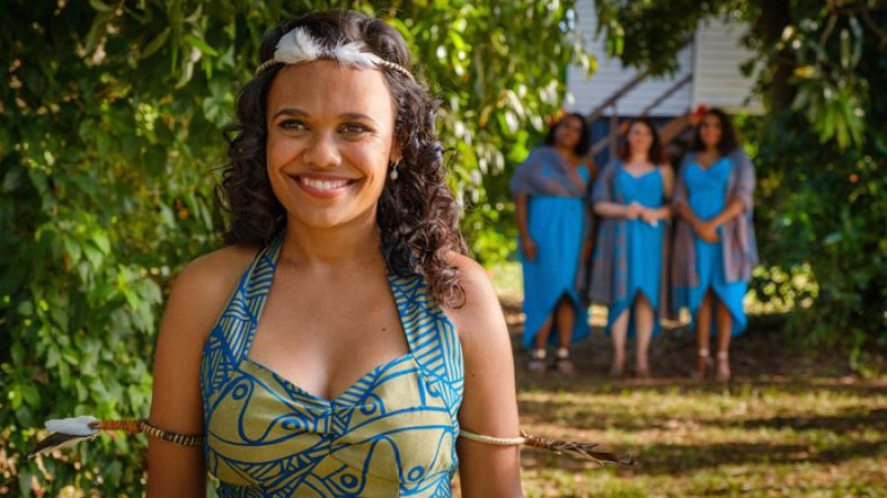 A bride is in traditional Tiwi wedding dress, of bright blue and lime green and is smiling towards the camera. She is outside on a sunny day and there are 3 bridesmaids in blue dresses in the background.
