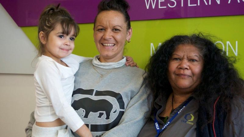 Two Indigenous adult women, one dressed in light grey shirt and holding a child dressed in white clothes, the other in a dark grey shirt.