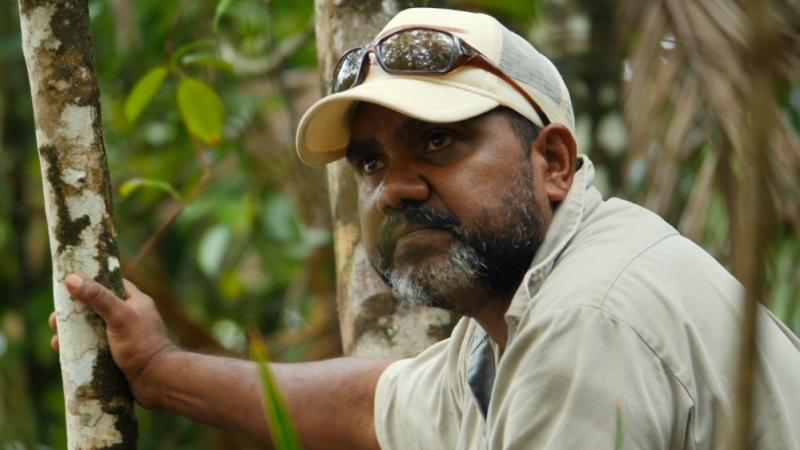 Middle aged Indigenous man with beard wearing a pale shirt and hat with sunglasses on his head leans against a small tree. In the background is foliage.