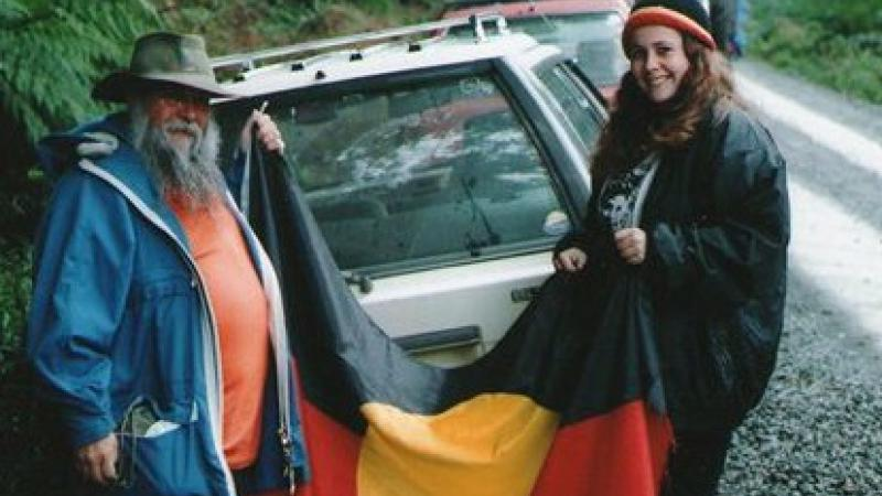 Trish and her father holding the Aboriginal flag while standing in front of a car.
