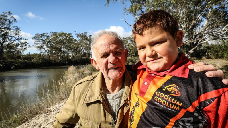 An Aboriginal man in brown jacket and boy in red, black and yellow shirt, stand near a river behind them. Also in the background are trees, grass and a blue sky.