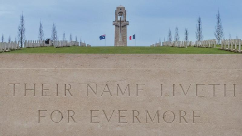 Tall tower flanked by Australian and French flags and to left and right are cemetery headstones with trees in the background. In the foreground is a carved stone with the words Their Name Liveth For Evermore