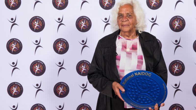 Elderly Indigenous woman, dressed in dark brown over coat and pink and white blouse, holding a blue award in the shape of a plate.