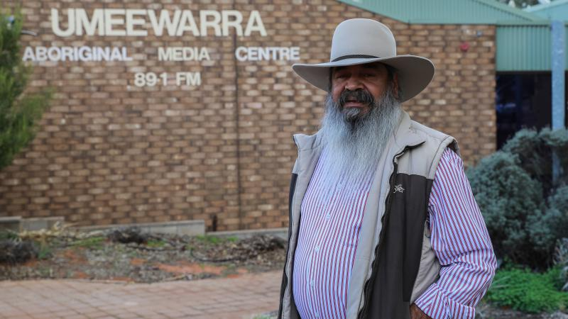 Aboriginal man with long white beard wearing a hat, striped shirt and vest stands in front of a brick building with the following words on the wall: Umeewarra Aboriginal Media Centre 89.1 FM.