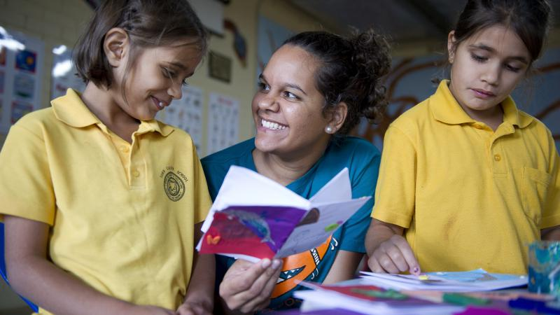 Indigenous woman in blue top holds a book as she sits between two Indigenous children in yellow tops.