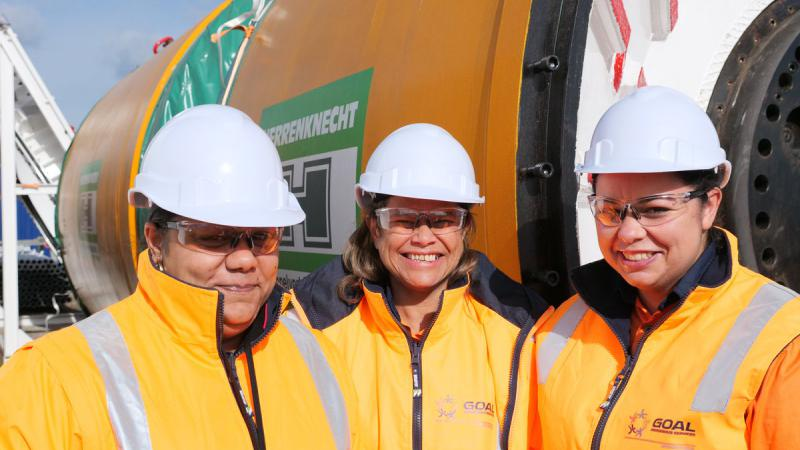 Three smiling Indigenous women in yellow jackets and white helmets stand in front of a large yellow, green and white machine.