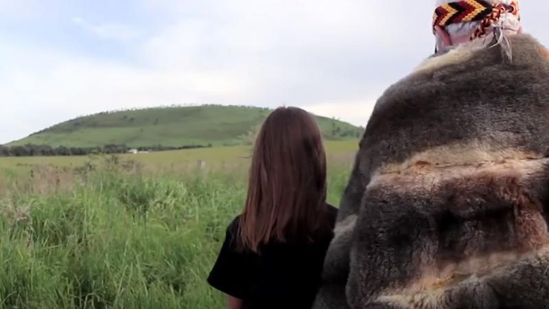 In the foreground we see the backs of an elderly man in a fur cloak and a young girl in a black shirt. Immediately in front of them is long grass and in the background is a large grass covered hill.