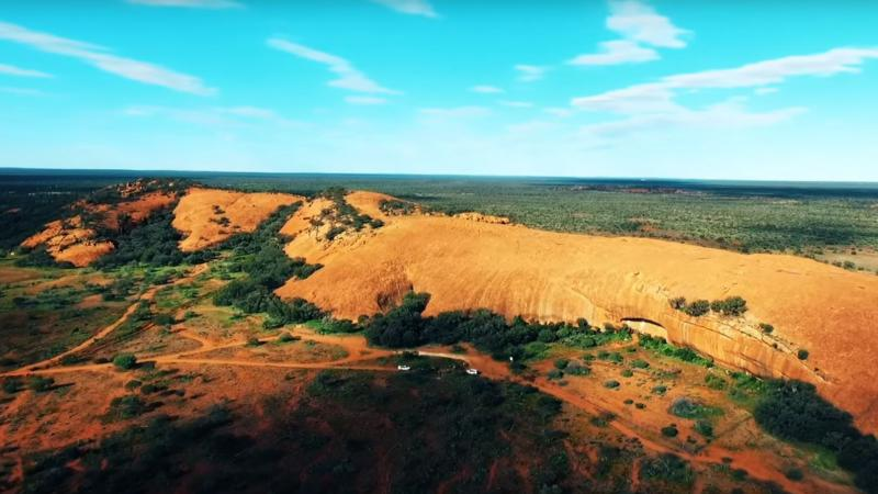 Large ochre coloured rock lies on a plain of ochre coloured soil and bushland.