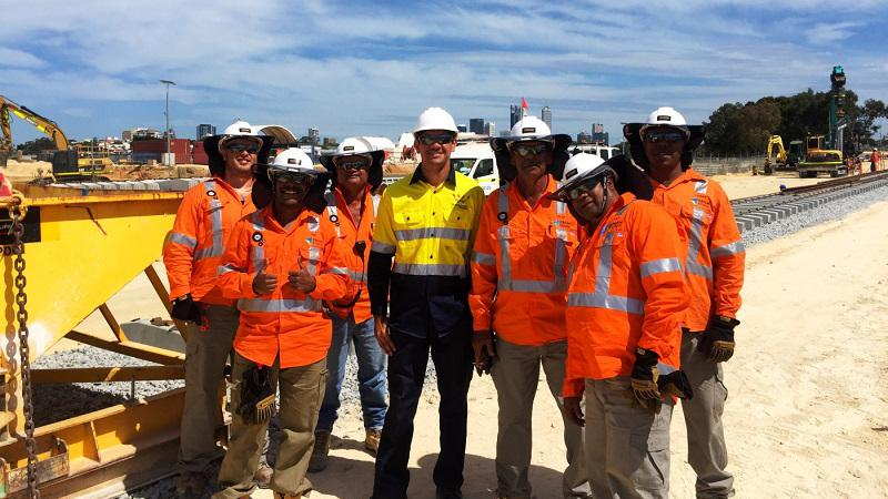 A group of seven men at a construction site, wearing high-vis vests and hard hats.