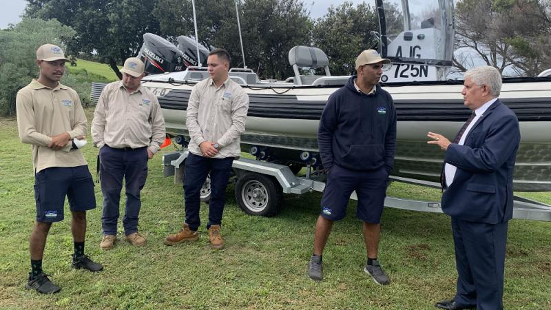 Five men stand in front of a large boat on a trailer on grass. In the background are trees. Four men are dressed in ranger uniforms and the fifth is wearing a suit.
