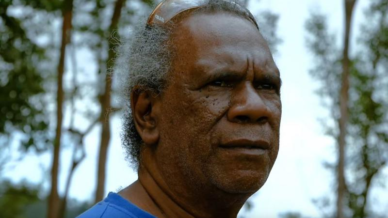 A head photo of an Indigenous man in blue shirt with sunglasses on his head. In the background are trees and sky.