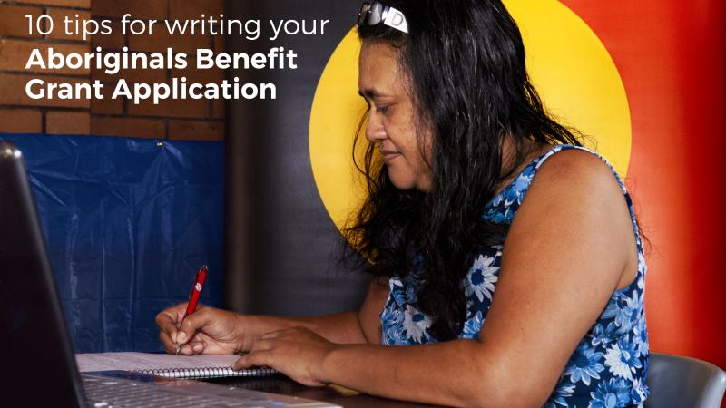 Indigenous woman writing on paper with a pen and the Aboriginal flag in the background, a laptop computer in the foreground and the following words displayed: 10 tips for writing your Aboriginal Benefit Grant Application