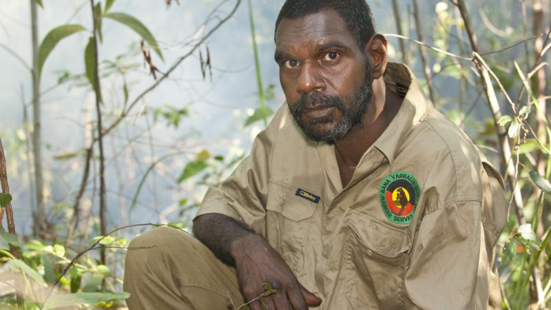 Indigenous man dressed in a ranger uniform sits in foreground with foliage in the background.