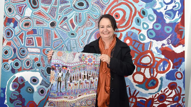 Cheryl Moggs, wearing a black jacket and orange scarf, holding the 2018 NAIDOC week poster 'tarumunggie – woman.' She is standing in front of a large, colourful canvas artwork.