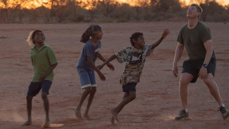 Three Aboriginal children and a non-Aboriginal man look upward on a dusty field with trees in the background.