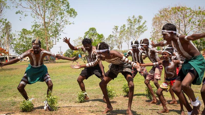 Group of young Aboriginal men in traditional wear and body paint dance on a grass and soil surface. In the background are trees and a building.