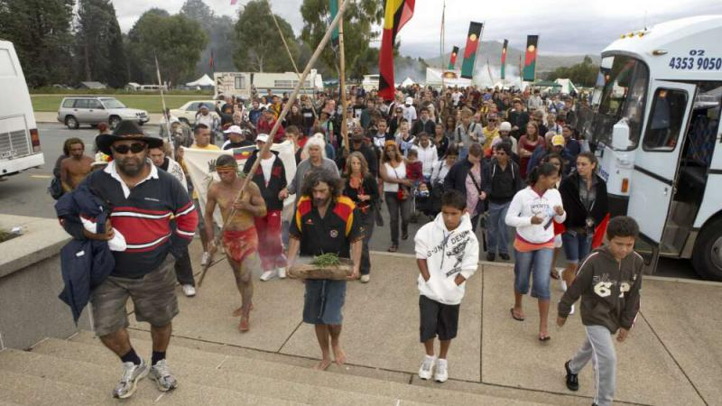 Large crowd of Indigenous men and women walking up stairs away from the Aboriginal Tent Embassy bearing Aboriginal flags coloured black on top and red on the bottom with a yellow circle. One man in a black shirt with red and yellow panels carrying a piece