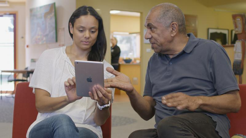 A young adult woman sits on a red chair holding a small tablet device. She is showing the screen to an older man who is gesturing to the device with his hand. They look calm and relaxed.