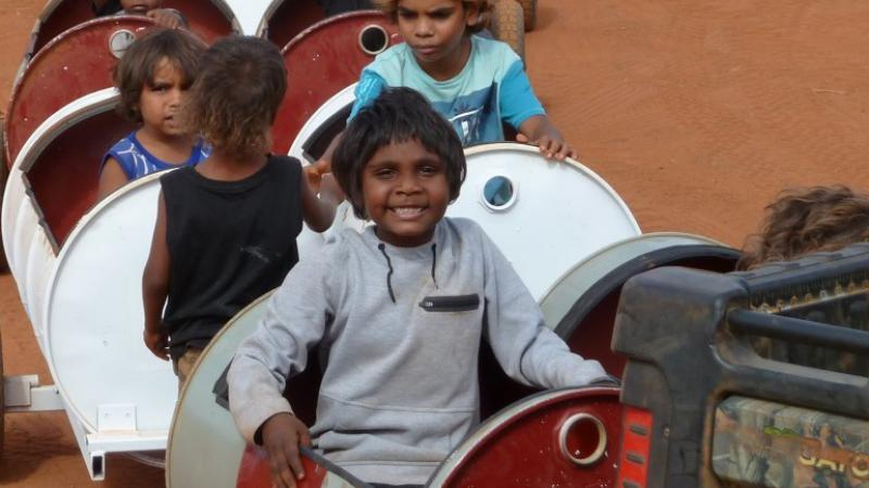 Young Aboriginal children sit in and stand next to a series of barrels mounted on wheels.
