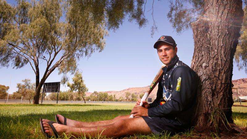 Young Aboriginal man in dark blue hat, shirt and shorts sits under a tree leaning up against the trunk while holding a cricket bat. In the background is a grassed area, a sign, many trees and a large brown hill.
