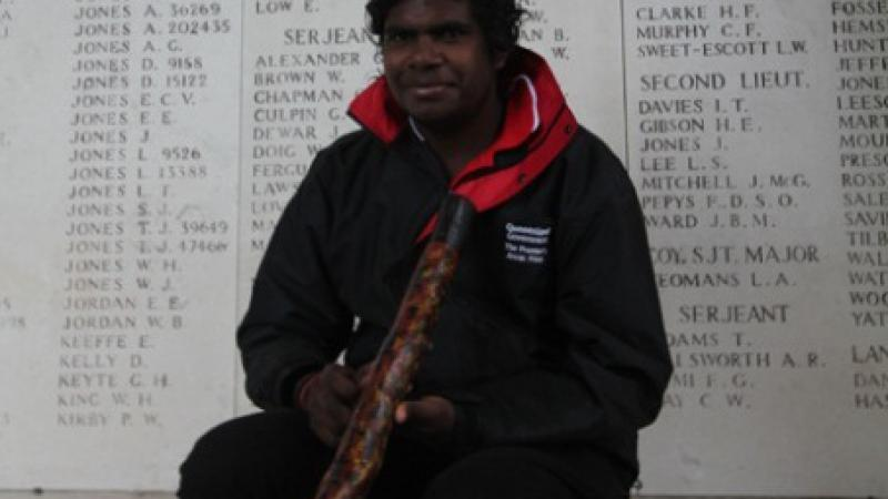 Elijah Douglas, holding his didgeridoo, sits in front of a wall of remembrance.