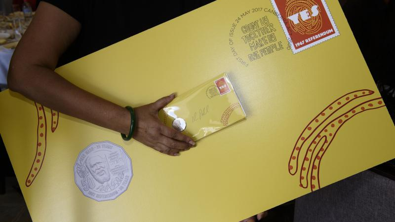 Indigenous person holding a large yellow envelope with 'Yes' stamp and new Eddie Mabo coin attached along with a regular size envelope of the same design. The envelope includes some Indigenous design.