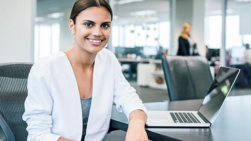 Female businesswoman smiling to camera sitting at desk with laptop open