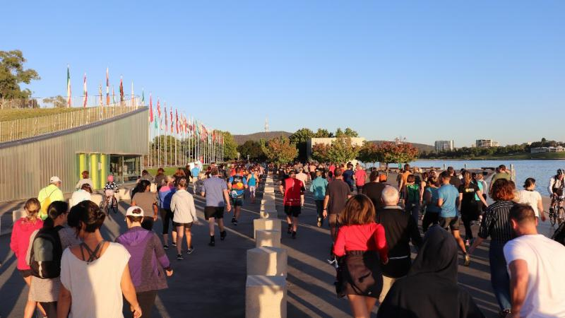 Large group of people in different exercise wear walk along a path next to a lake on the right and a building on the left behind which are many flags on poles and all in a line.