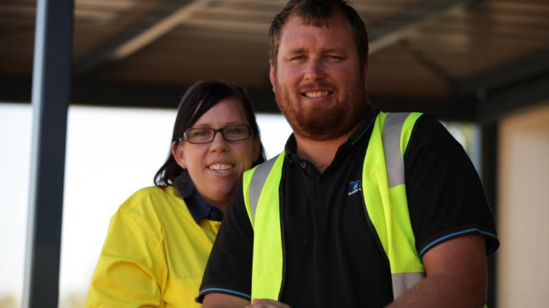 Woman in yellow shirt standing to left and behind man in dark shirt with safety vest.
