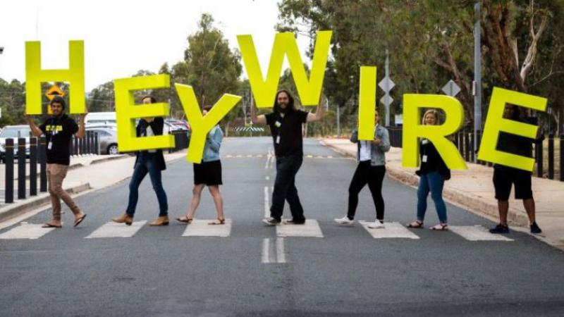Seven youth walk across a zebra crossing, each carrying large yellow letters which spell out Heywire. In the background are trees and cars and road.