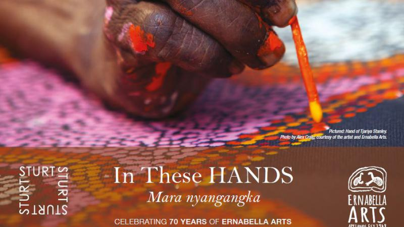 A paint splattered hand holds a paint brush over a painting of coloured dots. Included on the image are the following words: In These Hands Mara nyangangka celebrating 70 years of Ernabella Arts Sturt Gallery 7 December 2017 - 11 February 2018.