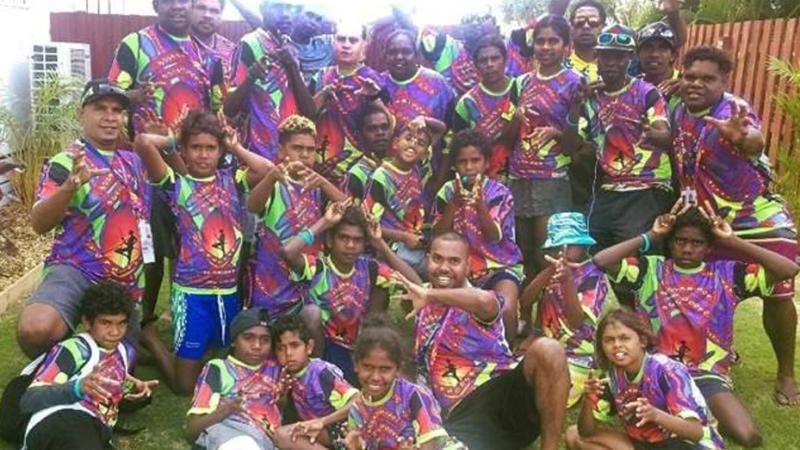 Aboriginal adults and youth in colourful shirts sitting on grass.