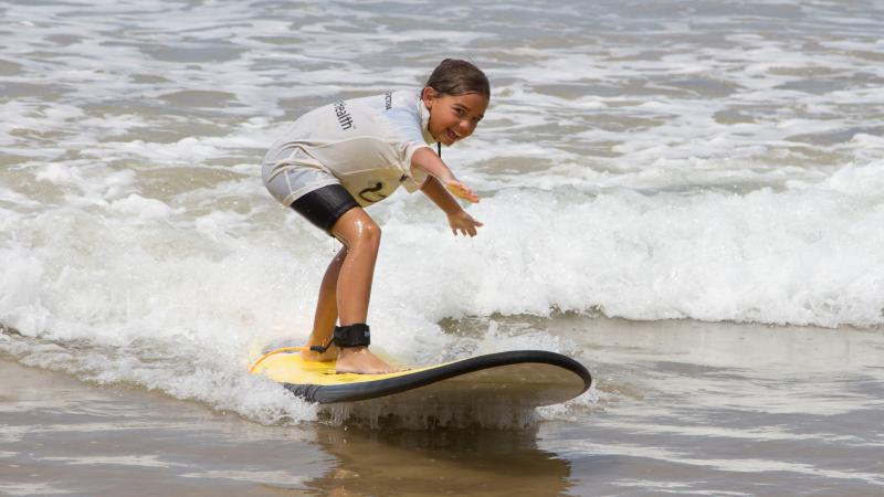 Young Aboriginal child in black shorts and white shirt stands on a surfboard riding a half-metre high wave.