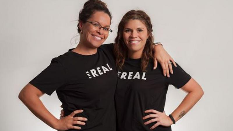 Two women in black t-shirts stand arm in arm. on the shirts is printed The Real.