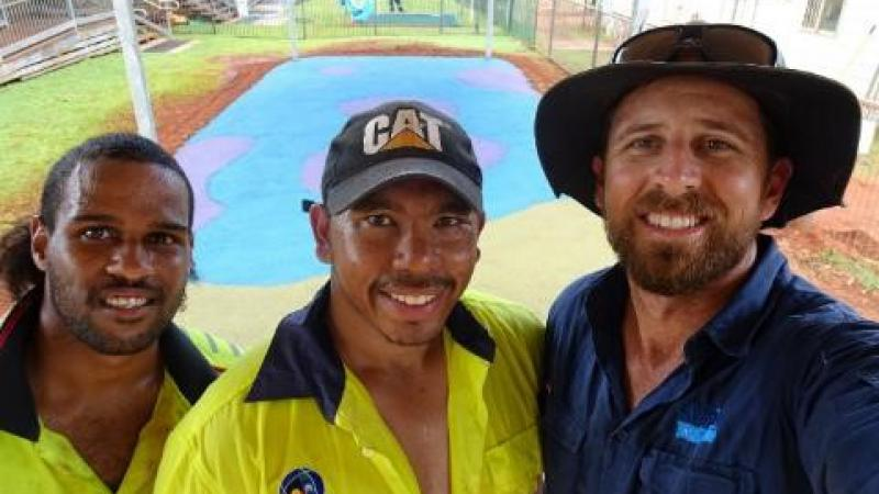 Three men, two in yellow work-wear shirts and one in a blue shirt stand close to camera. In the background is a flat area covered with blue and pink rubber. Surrounding this is bare soil, grass and fences. There are buildings at right and left and behind.
