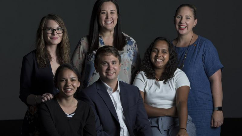 Group of 5 Indigenous women and one Indigenous man smiling to camera in front of dark background.