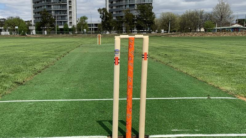 Two sets of cricket stumps and bails stand at each end of a narrow green strip of artificial grass. The two middle stumps are bright orange with Indigenous designs. On both sides of the pitch is real grass and in the background are two tall buildings.