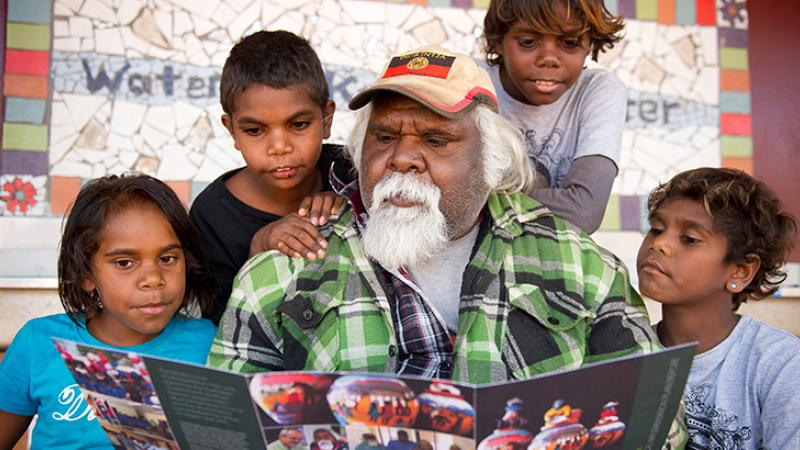 Man reading a book to a group of children