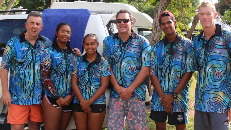 6 adults (2 female and 4 male / 3 Aboriginal) dressed in blue shirts featuring Indigenous designs stand in front of a white car on grass with trees in the background.
