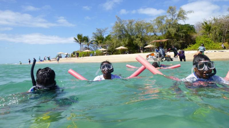 Three Indigenous people wearing snorkles and diving masks, and holding floating noodles swim in seawater. In the background is sand, beach umbrellas, trees and other people.