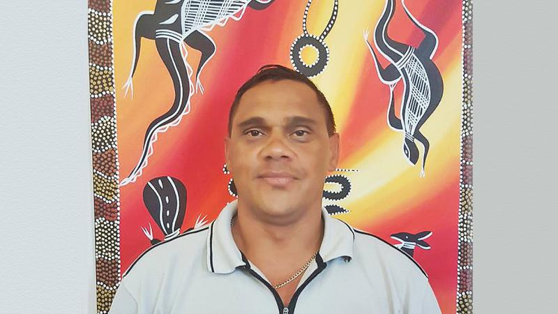 Young Aboriginal man in pale blue shirt stands in front of Indigenous artwork displaying dark brown and white animals on a red and yellow background.