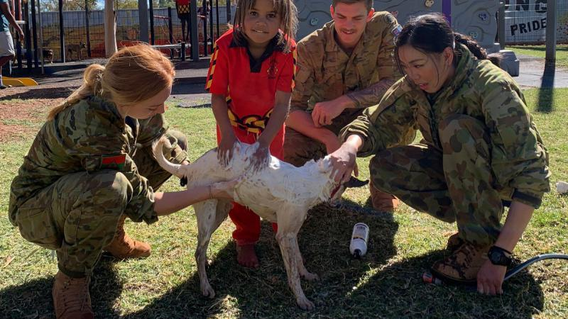 Young Aboriginal girl in red school uniform and three soldiers (2 women and 1 man) surround a white dog on a grassed area. One soldier holds a hose. In the background is a playground.