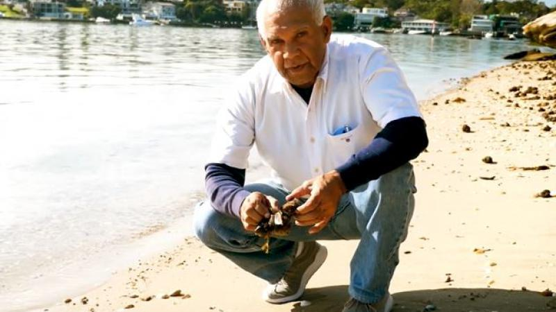Elderly Aboriginal man in white shirt and jeans squats next to a river on a sandy shore. In the background on the other side of the river are houses and trees.