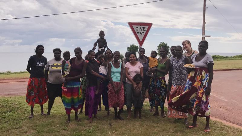 A group of mainly Aboriginal women and children dressed in an array of colourful clothing stand on grass next to a road corner with a telegraph pole in the background and a sign that says Give Way.