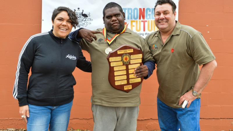 Jameson (centre) with his volunteer award at the Stronger Futures Alice 3on3. Pictured with role model Jacinta Price and Vibe Australia Managing Director, Gavin Jones.