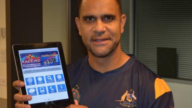 "AFL Indigenous All Stars coach Michael O'Loughlin with the ""Aboriginal Health in Aboriginal Hands"" app."